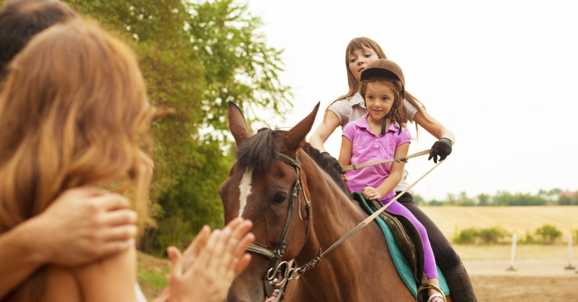 Child Riding Horse Outdoors. Little girl with riding hat learning how to ride a horse. Riding horse together with her instructor. Mother and father watching and encourage her.