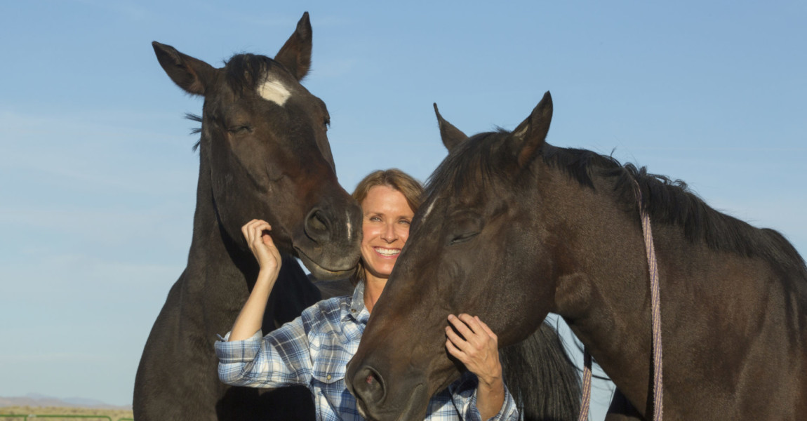 Caucasian rancher smiling with horses Caucasian rancher smiling with horses