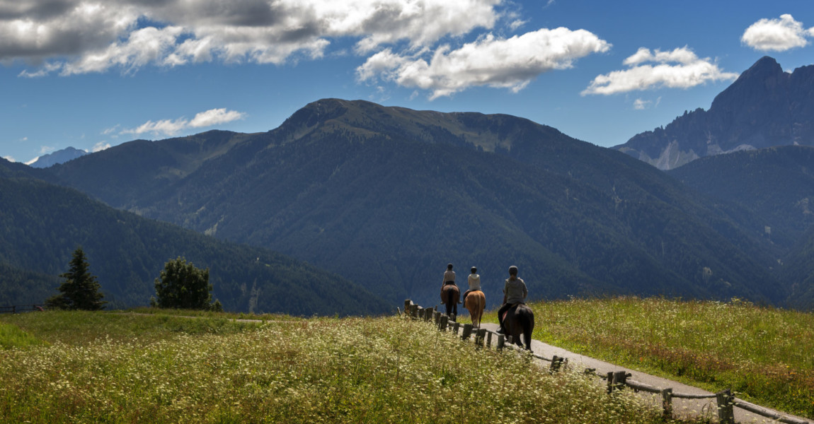 three people ride over the mountains