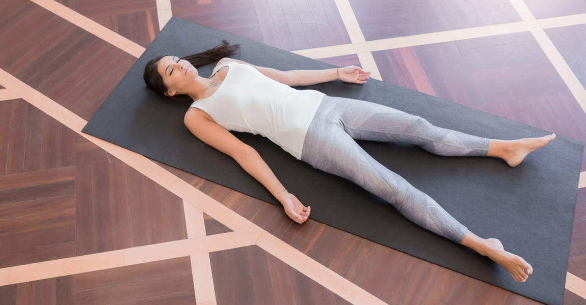 Young woman meditating on a wooden floor Top view Young woman meditating on a wooden floor and lying in Shavasana pose. View from above of attractive yogi working out, doing yoga exercise on black mat. Lifestyle