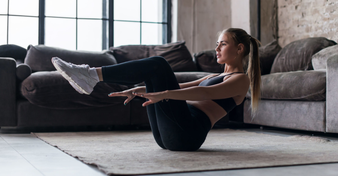 Slim sporty girl doing v-ups abs workout at home Slim sporty girl doing v-ups abs workout at home.