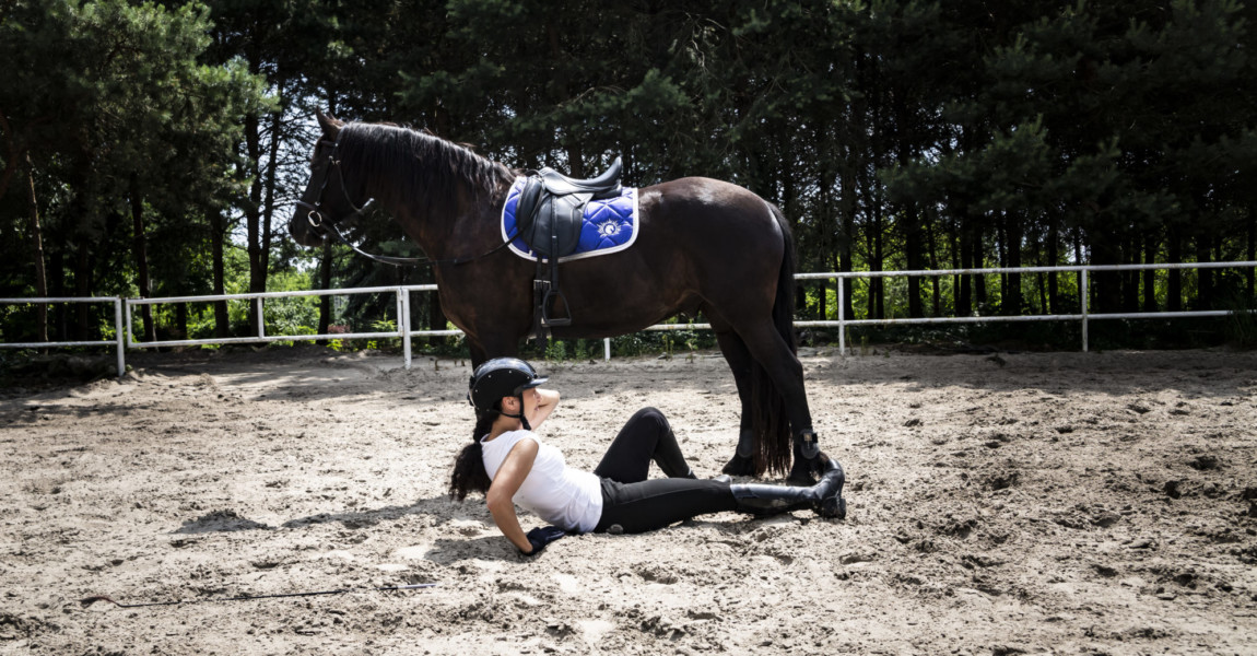 Falling from a horse. Riding accident. Injured woman The woman rider fell off his horse.